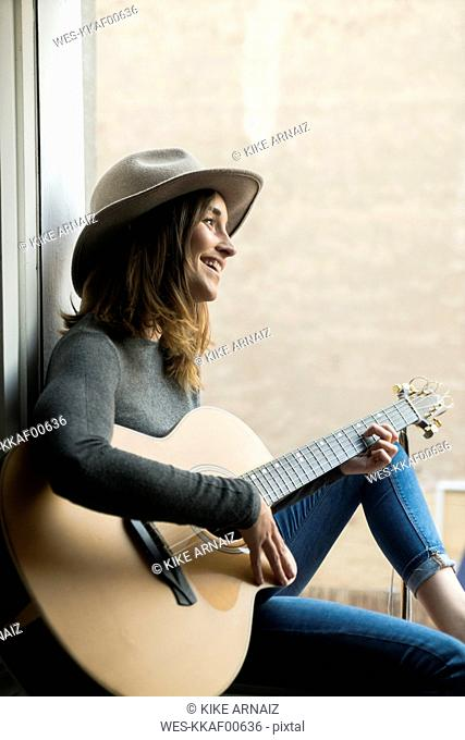 Smiling young woman sitting in window frame playing guitar