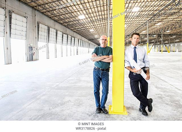 Two Caucasian men standing in front of loading dock doors in a new warehouse interior