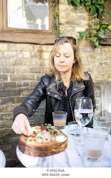 Mature woman having cold cuts at outdoor cafe