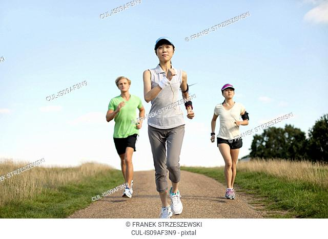 Three young adults jogging along field track