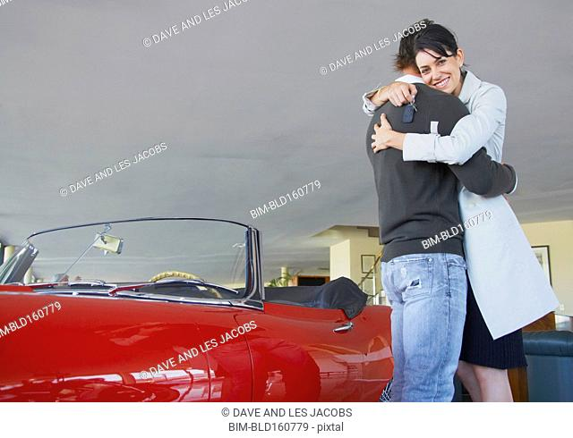 Caucasian couple hugging near convertible