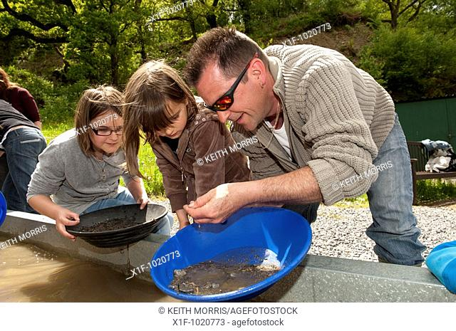 Father and two daughters panning for welsh gold at Dolaucothi Gold Mine, National Trust, Carmarthenshire, west wales, UK
