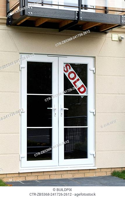 Sold sign on French doors of a new ground floor apartment, Benfleet, Essex, UK