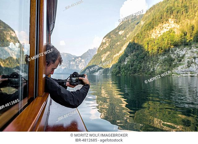 Man, tourist photographing from excursion ship at Königssee, National Park Berchtesgaden, Berchtesgadenener Land, Upper Bavaria, Bavaria, Germany