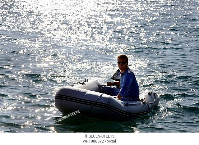 Man steering yacht dinghy, Dalmatia, Croatia, Europe