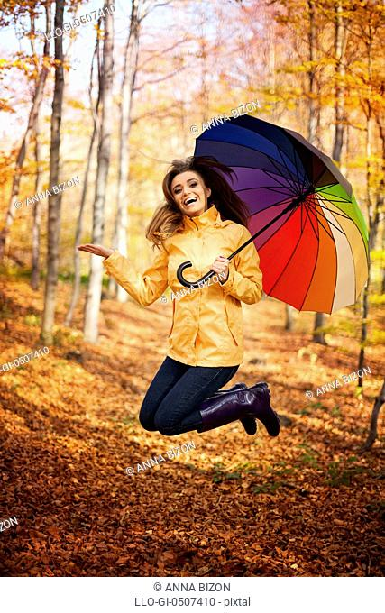 Young woman jumping during the rainy day at autumn, Debica, Poland