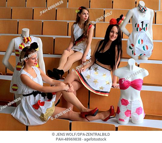 Models Christina (L-R), Josephine and Vivien present dresses on occasion of the upcoming soccer world championship at the 'Schule für Mode und Design' (lit