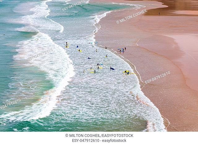 Surfers in the waves off Mawgan Porth Beach, Cornwall, UK
