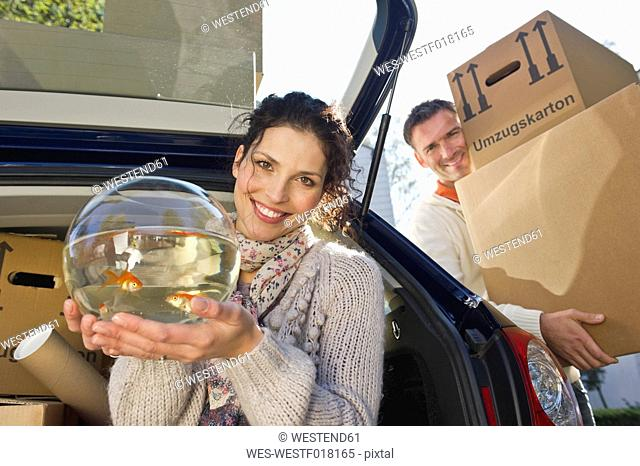 Germany, Bavaria, Grobenzell, Woman holding goldfish bowl with man in background, smiling, portrait