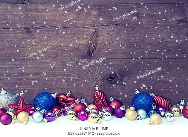 Christmas Card With Multi Colored Christmas Treee Balls On White Snow, Snowflakes. Christmas Decoration Infront Of Wooden Brown Background