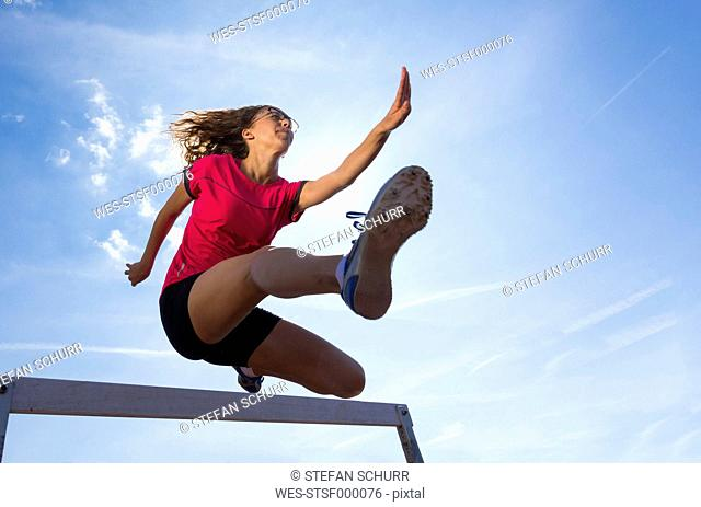 Germany, Young woman athlete jumping hurdles on track