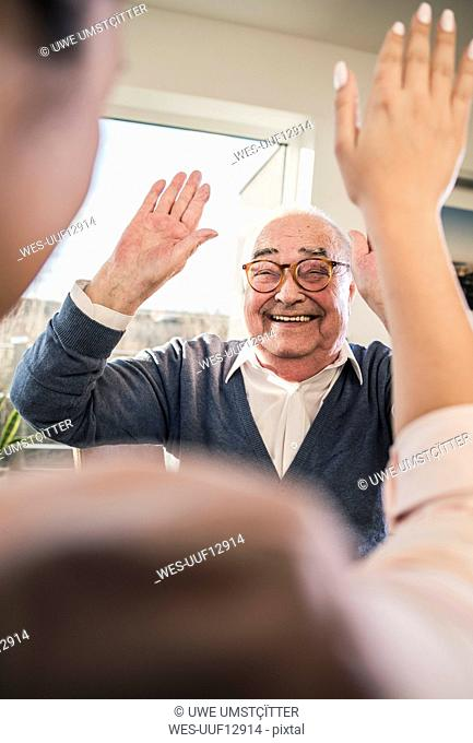 Happy senior man with raised hands looking at young woman