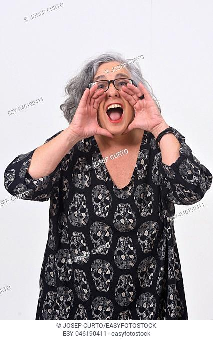 woman putting a hand in mouth and is screaming on white background
