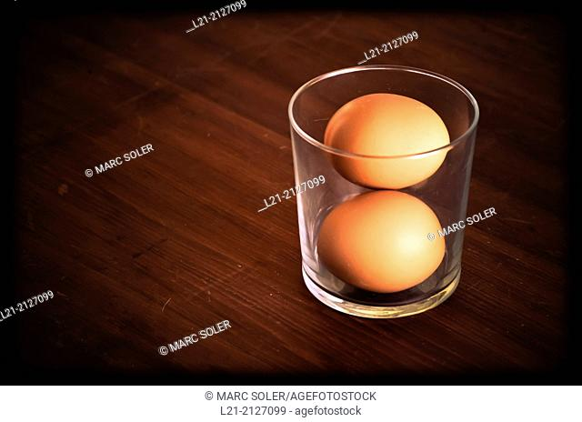 Two brown eggs inside a glass