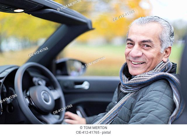 Portrait smiling, confident senior man in convertible