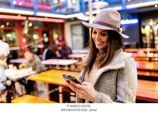 Portrait of smiling young woman looking at her smartphone