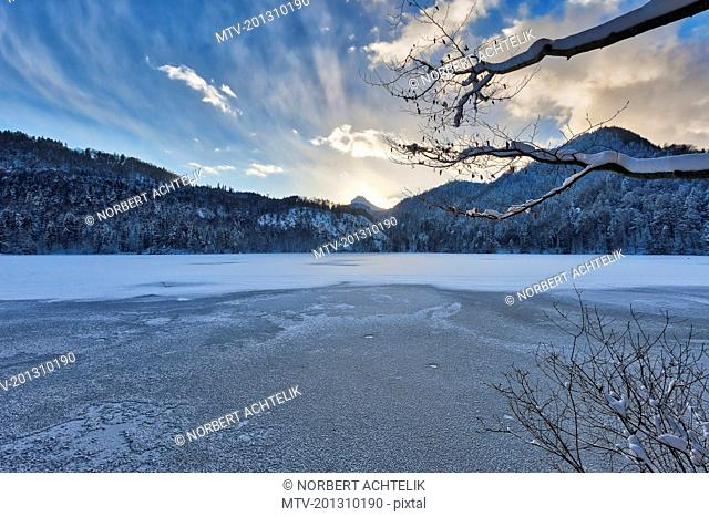 Scenic view of frozen Hechtsee lake with snow covered trees and mountain