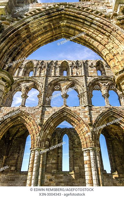 Archways frame ruins of Whitby Abbey against blue skies, Whitby, Yorkshire, UK