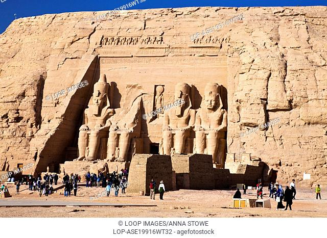 Tourists at the famous site of the Great Temple at Abu Simbel in Egypt are dwarfed by the huge statues of Ramesses II