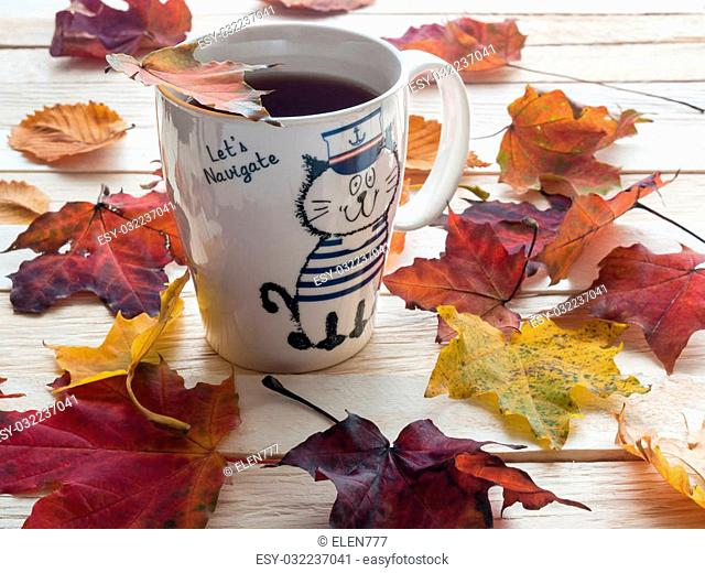 Beautiful and colorful autumn leaves and white cup of tea standing on a table made of wooden plank