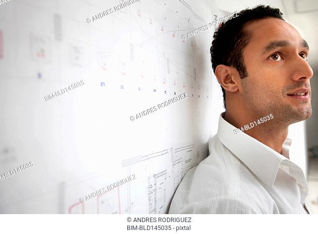 Serious Hispanic businessman leaning against blueprint