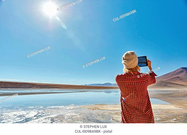 Woman photographing landscape, using digital tablet, Salar de Chalviri, Chalviri, Oruro, Bolivia, South America