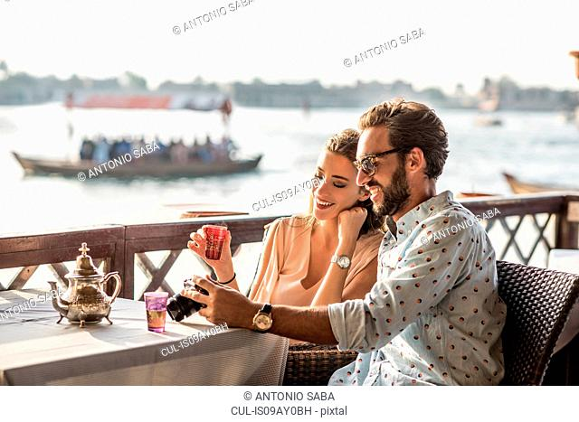 Romantic couple reviewing camera at Dubai marina cafe, United Arab Emirates