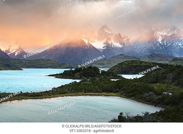 Pehoé Lake with Paine Horns and Cerro Paine covered in mist at dawn. Torres del Paine National Park, Ultima Esperanza province, Magallanes region, Chile