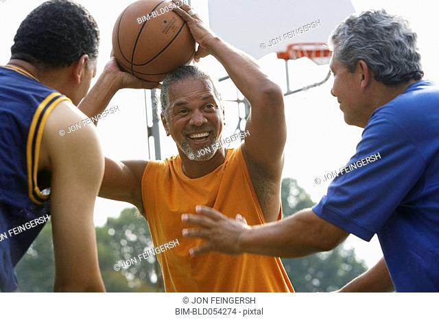 Multi-ethnic men playing basketball