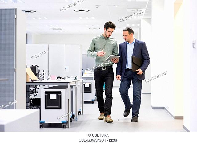 Two businessmen on the move looking at digital tablet in office