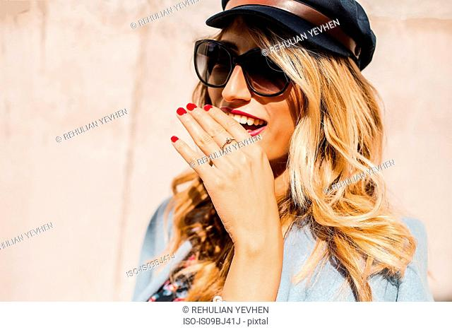 Blond, stylish mid adult woman wearing sunglasses in front of wall with hand covering mouth