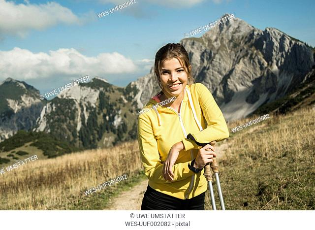 Austria, Tyrol, Tannheim Valley, smiling young woman holding nordic walking sticks in mountains