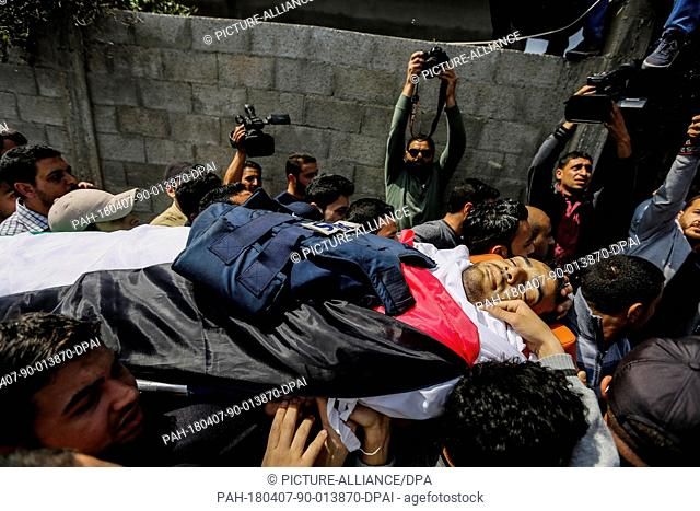 Palestinian journalists and mourners carry the body of Palestinian journalist Yasser Murtaja, who was killed during clashes with Israeli Security Forces near...