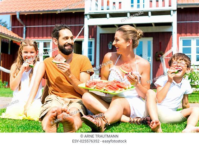 Familie sitzt im Gras vor ihrem Haus und isst Wassermelone als Erfrischung im Sommer