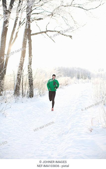 Mid adult man running at winter
