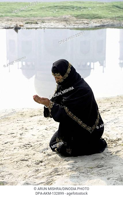 499b43a552aa A Muslim woman offering namaz in front of mogul monument Taj Mahal seven  wonder of the