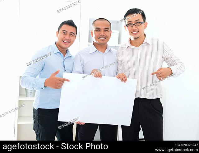 Asian business team holding a blank banner