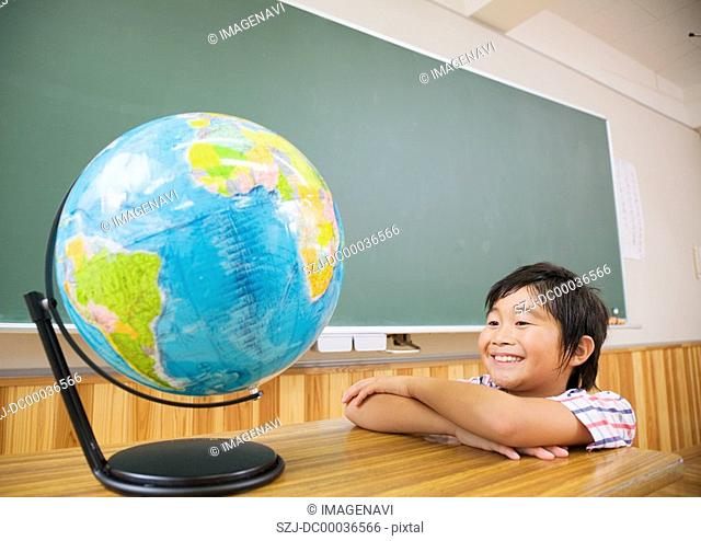 Elementary school boy looking at terrestrial globe