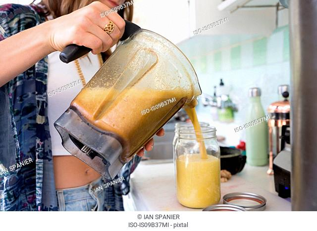 Cropped view of woman pouring smoothie from food processor jug