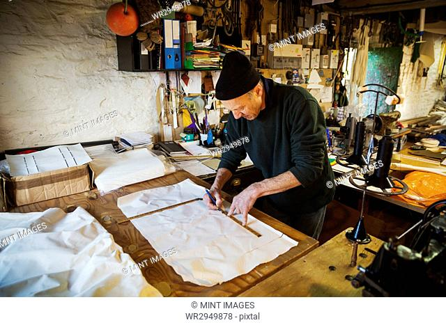 Man in a sailmaker's workshop measuring a piece of fabric for a sail