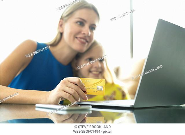 Mother and daughter using laptop and credit card together