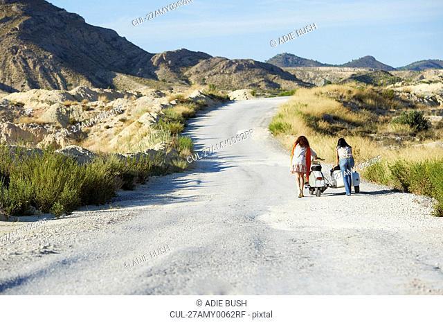 Women pushing motorbike and sidecar