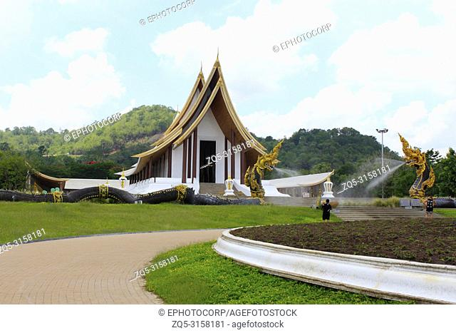 Side angle of the white Buddhist temple with dragon fountains and a pathway at Ban Nong Thailand