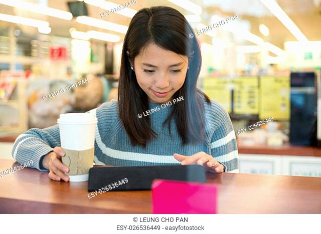 Woman drinking coffee and using tablet computer in coffee shop