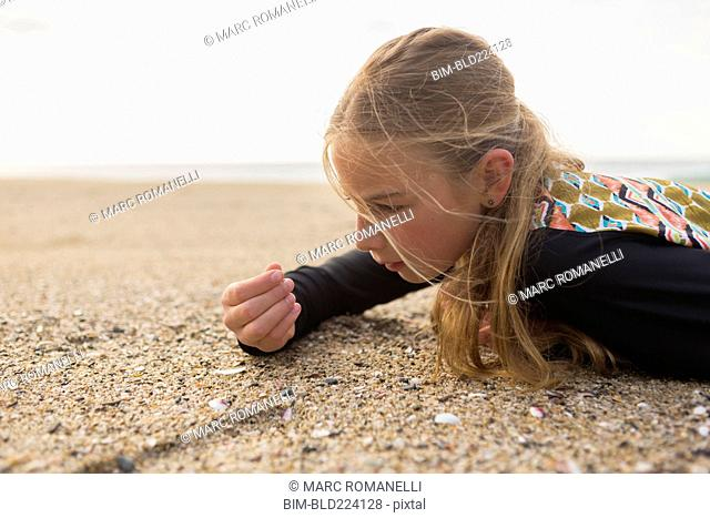 Caucasian girl laying on beach examining seashells