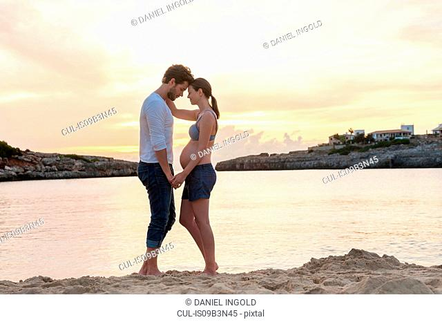 Pregnant woman and man, standing face to face on beach, holding hands