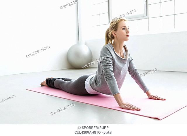 Young woman in yoga pose on yoga mat