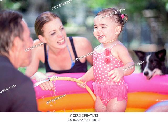Parents and daughter in inflatable pool, dog looking on