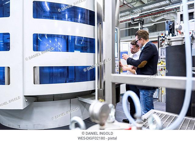 Two men talking in factory shop floor looking at screen