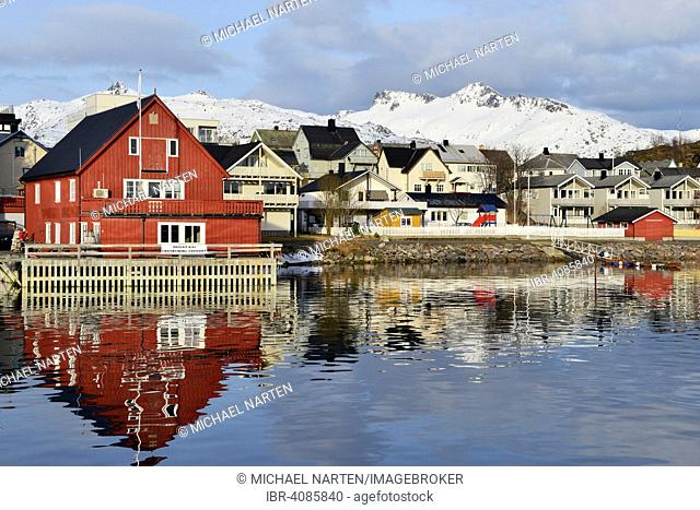 Red house with a private waterfront and several houses in the village, snow-covered mountains at the back, Svolvær, Lofoten, Nordland, Norway